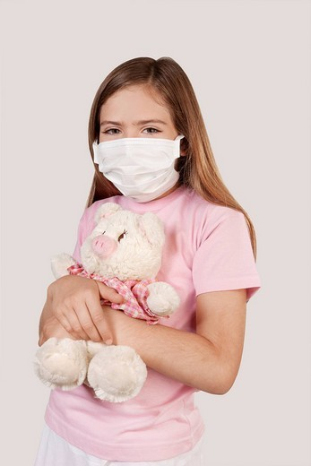 Girl wearing flu mask and holding a stuffed toy : Stock Photo