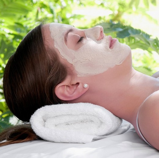 Woman with facial mask lying on a massage table : Stock Photo