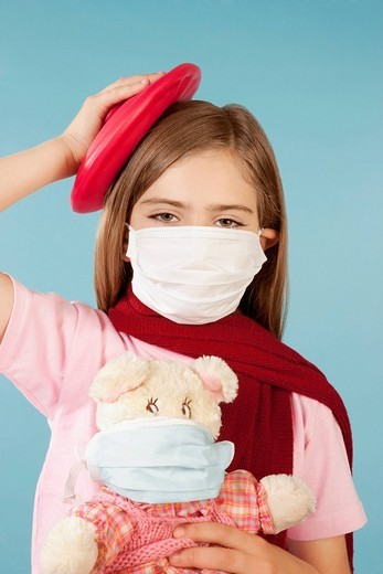 Portrait of a girl wearing a flu mask and applying an ice pack on her head : Stock Photo