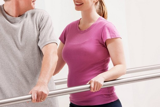 Physiotherapist assisting a patient in walking : Stock Photo