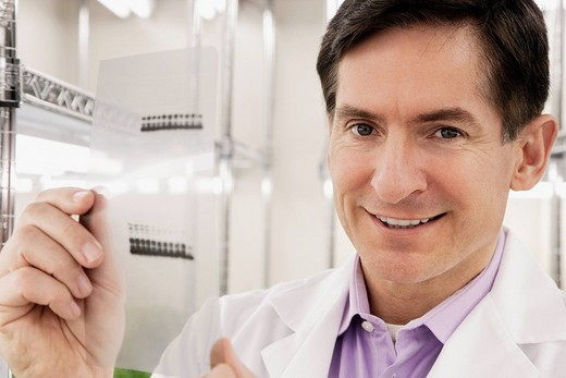 Scientist holding a report in a laboratory and smiling : Stock Photo
