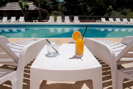 Lounge chairs with juices on table at the poolside : Stock Photo