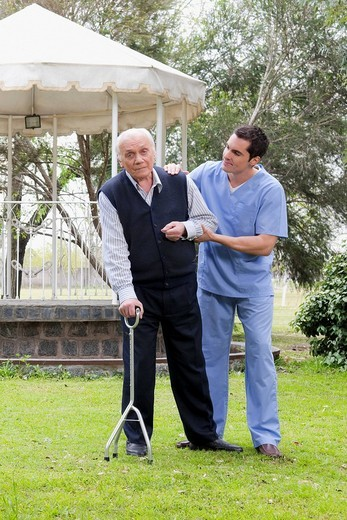Healthcare worker assisting a patient in walking : Stock Photo
