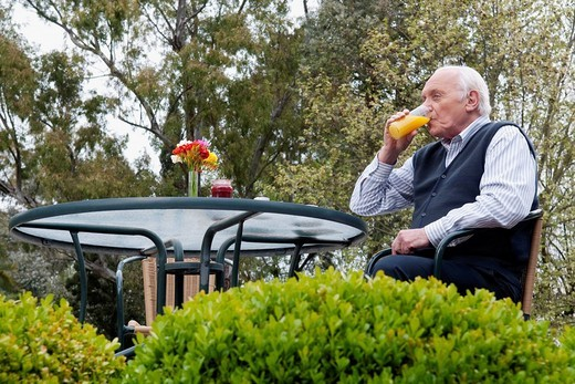 Senior man sitting on chair and drinking juice : Stock Photo