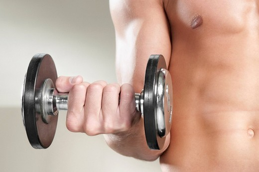 Close_up of a man exercising with dumbbells : Stock Photo