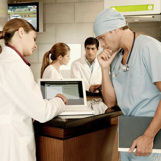 Female doctor and a surgeon discussing a medical report on a laptop : Stock Photo