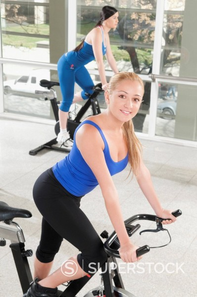 Stock Photo: 4105-5192 Two women working out on exercise bikes in a gym