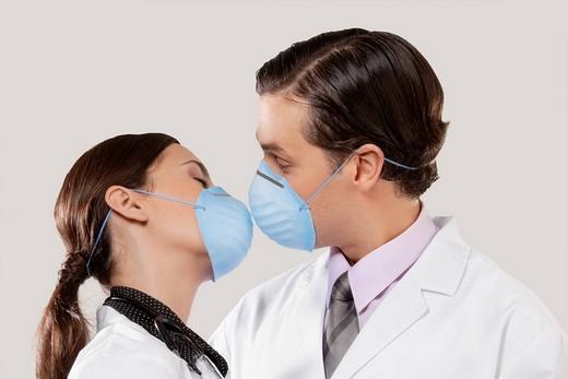 Doctors wearing flu masks and romancing : Stock Photo