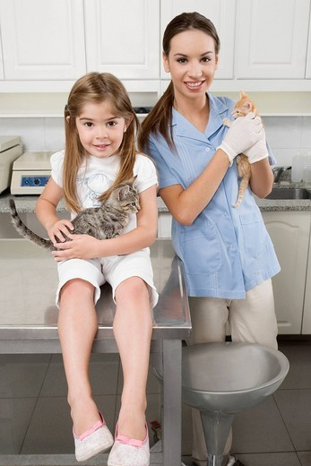 Female vet with a girl carrying cats : Stock Photo