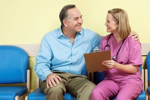 Female nurse showing a medical report to a patient : Stock Photo