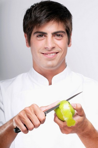 Man peeling a granny smith apple and smiling : Stock Photo