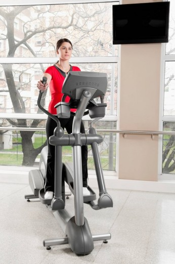 Stock Photo: 4105-6020 Woman working out on a stepping machine in a gym