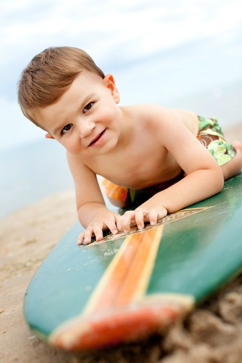 Stock Photo: 4111-203 Boy lying on a surfboard on the beach, Glen Arbor, Leelanau County, Michigan, USA