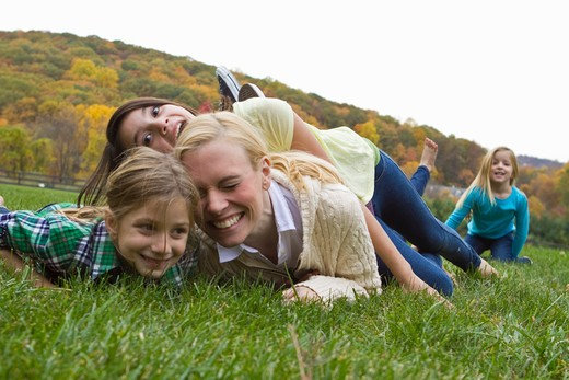 Mother playing with three daughters playing on grass : Stock Photo