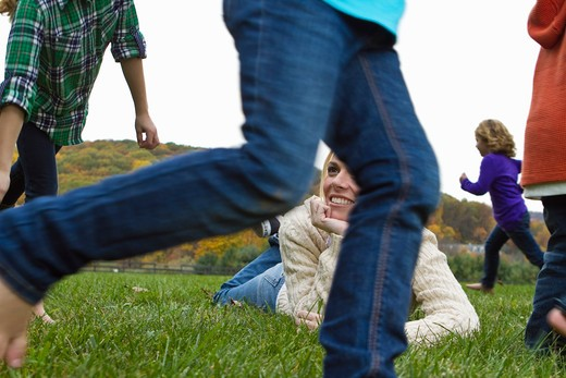 Woman lying on grass, children running around : Stock Photo