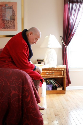 Stock Photo: 4113-210 Mature man sitting on bed looking serious