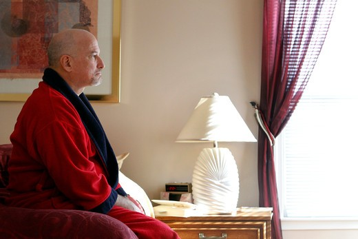 Stock Photo: 4113-211 Mature man sitting on bed looking serious