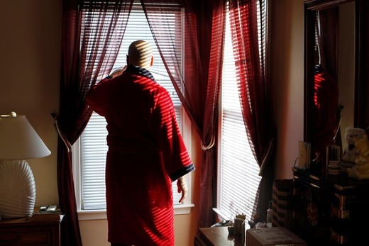 Mature man looking out of bedroom window : Stock Photo