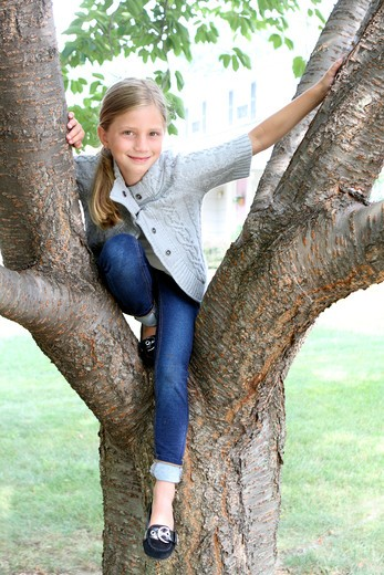 Stock Photo: 4113R-152 Girl sitting on a tree in a park