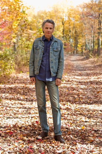 Portrait of man standing on Autumn forest track : Stock Photo