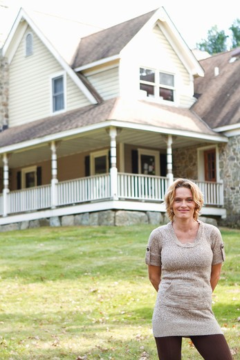 Portrait of smiling woman standing in front of large house : Stock Photo