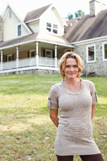 Stock Photo: 4113R-165 Portrait of smiling woman standing in front of large house