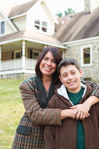 Stock Photo: 4113R-166 Portrait of smiling mother and son standing in front of large house