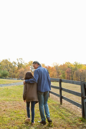 Rear view of father and daughter walking on field : Stock Photo