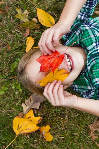 Smiling girl holding Autumn leaves in front of face, lying on grass : Stock Photo