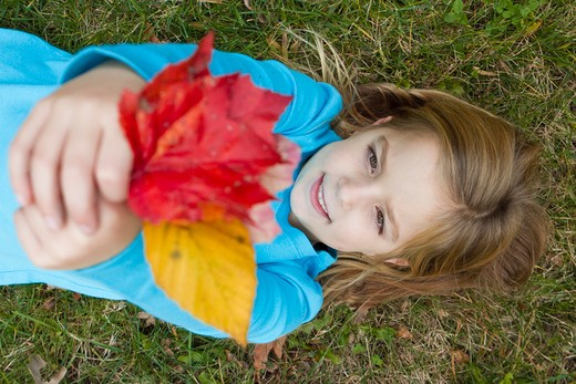 Smiling girl holding Autumn leaves, lying on grass : Stock Photo
