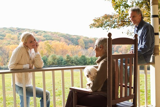 People with dog relaxing on porch in rural landscape : Stock Photo