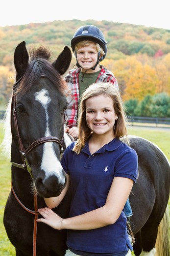 Stock Photo: 4113R-182 Portrait of girl assisting boy horseback riding