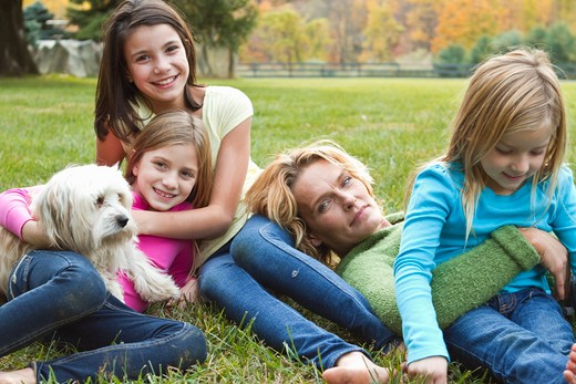 Mother with three daughters and dog relaxing on grass : Stock Photo