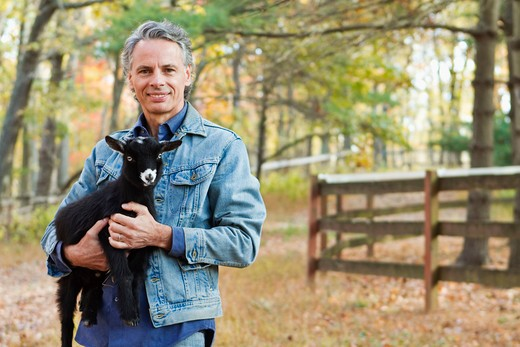 Portrait of farmer holding black lamb : Stock Photo