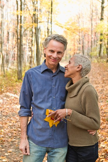 Mature couple holding Autumn leaves in forest : Stock Photo