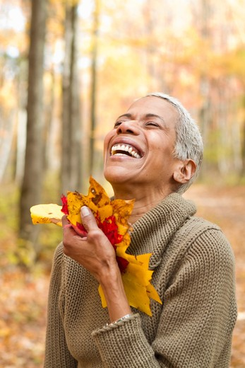 Portrait of mature woman holding Autumn leaves and laughing : Stock Photo