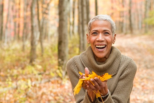 Stock Photo: 4113R-187E Portrait of mature woman holding Autumn leaves and laughing