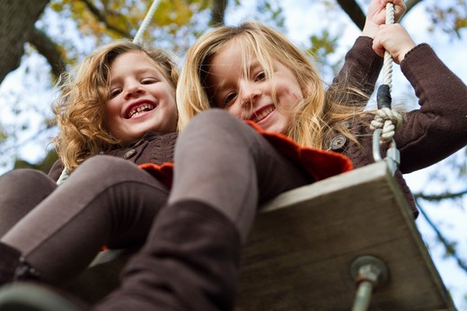 Portrait of two girls on swing : Stock Photo
