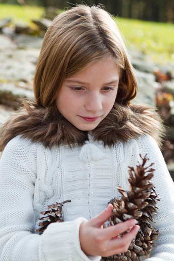 Portrait of girl holding pinecones : Stock Photo