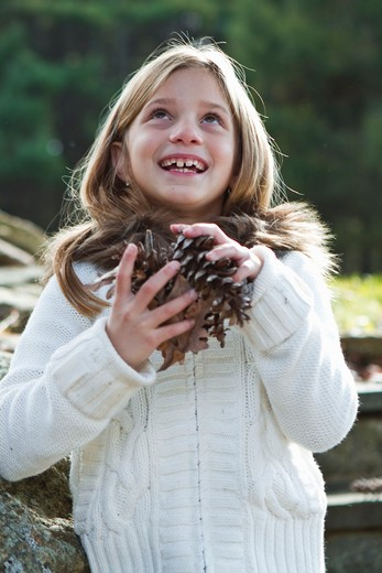 Stock Photo: 4113R-189C Portrait of girl holding pinecones