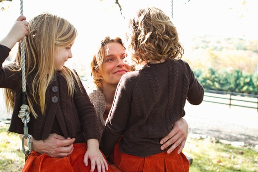 Stock Photo: 4113R-190C Mother with two daughters on swing