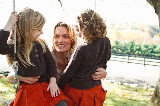 Stock Photo: 4113R-190D Mother with two daughters on swing