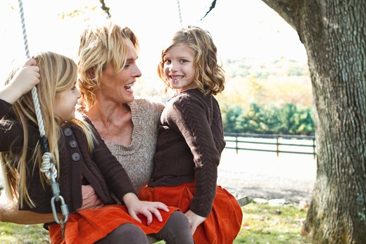 Stock Photo: 4113R-190H Mother with two daughters on swing