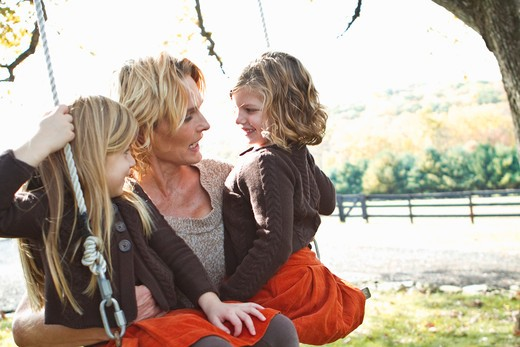 Mother with two daughters on swing : Stock Photo