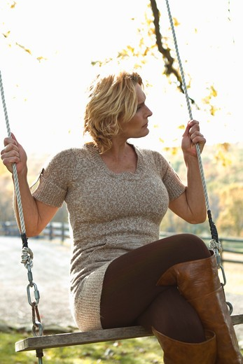Woman sitting on swing : Stock Photo
