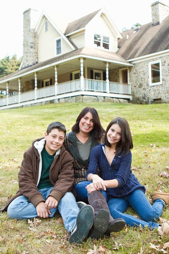 Stock Photo: 4113R-192B Portrait of smiling mother with two children sitting in front of large house