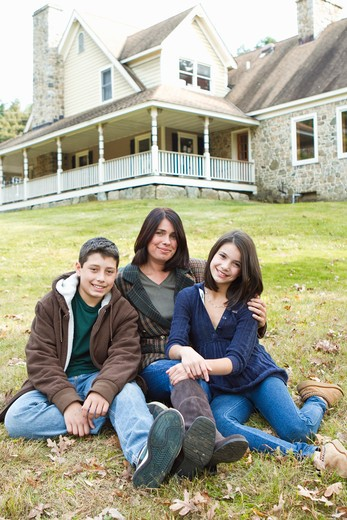 Portrait of smiling mother with two children sitting in front of large house : Stock Photo