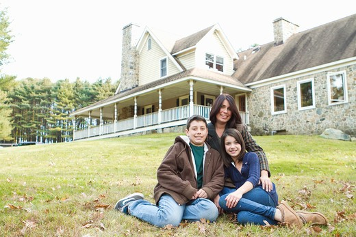 Stock Photo: 4113R-192D Portrait of smiling mother with two children sitting in front of large house