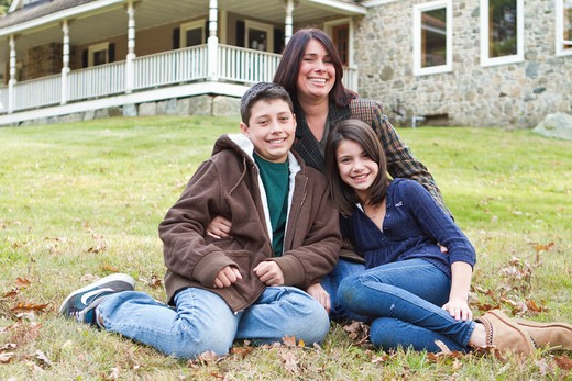 Stock Photo: 4113R-192E Portrait of smiling mother with two children sitting in front of large house