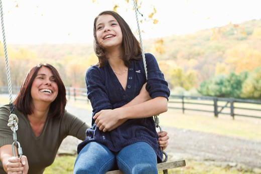 Mother with daughter on swing : Stock Photo
